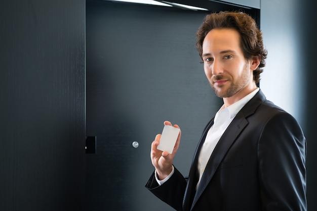ホテルの部屋のドアの前にキーカードを持って立っている若いビジネスマン