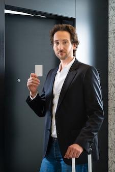 Молодой деловой человек, стоящий с карточкой-ключом перед дверью номера в отеле