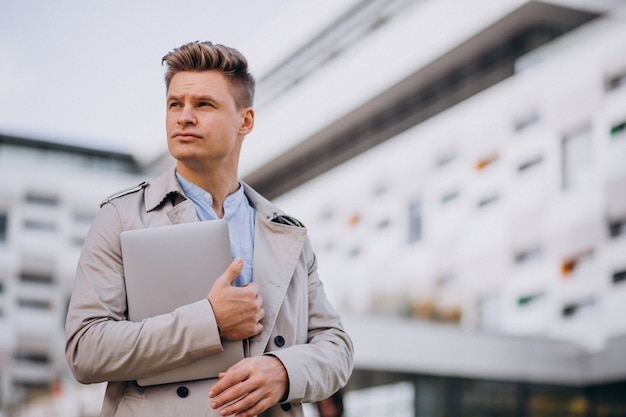 Young business man standing with laptop outside the business centre