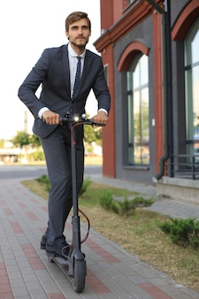 Young business man in suit riding on electric scooter on a business meeting. ecologic transport concept.