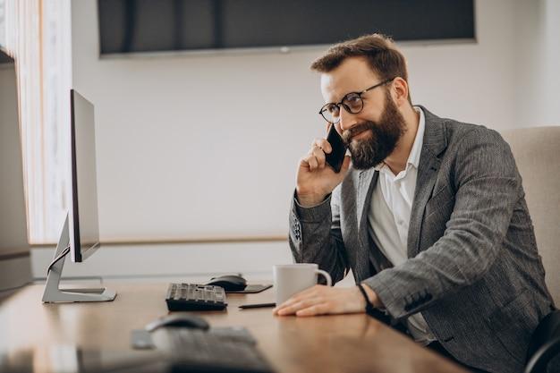 Молодой деловой человек разговаривает по телефону и работает на компьютере