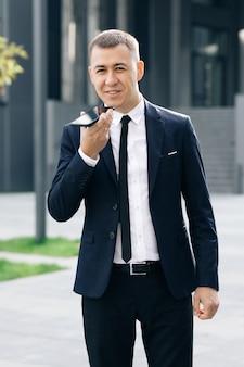 Молодой деловой человек разговаривает по телефону возле современного офисного здания