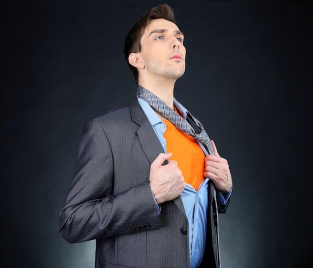Молодой деловой человек разрывает свою рубашку, показывая костюм супергероя на черном