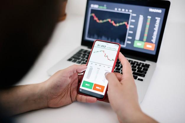 Молодой бизнесмен трейдер-инвестор с помощью приложения для мобильного телефона анализирует фондовый рынок криптовалюты