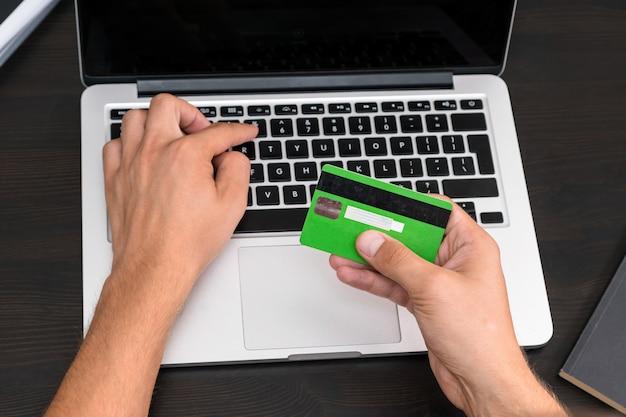 コンピューターのキーボードでクレジットカード情報を入力する若いビジネスマン。手に見えるクレジットカード。クローズアップ、営業所の職場。債務、請求書の支払い、デビットカード情報、オンラインバンキング、住宅ローン