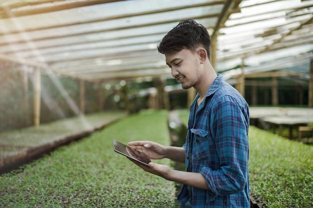 농장 디지털 및 스마트 농업 사진 개념을 확인하는 태블릿을 사용하는 젊은 사업가
