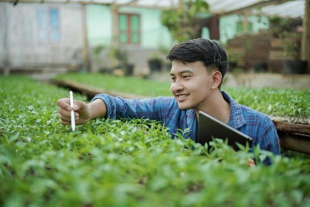 농장 디지털 농업 사진 개념을 확인하는 태블릿을 사용하는 젊은 사업가