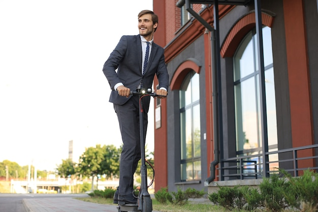 Young business man using electric scooter on city street. modern and ecological transportation concept.