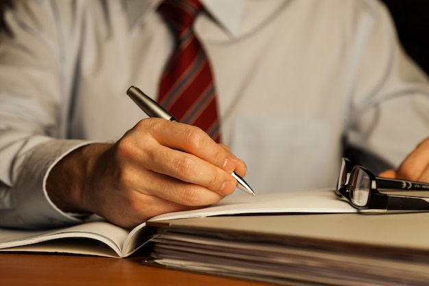 Young business man using pen and write text