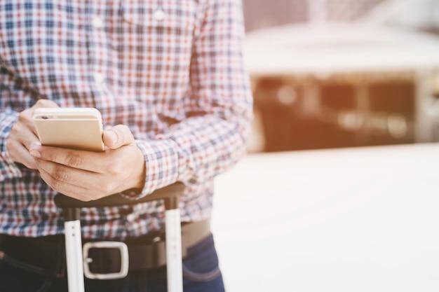 若いビジネスマンは格子縞のシャツを着ています。携帯電話で使用して手を閉じます。携帯スマートフォンでメッセージを見ながら立っています。ソフトフォーカス。