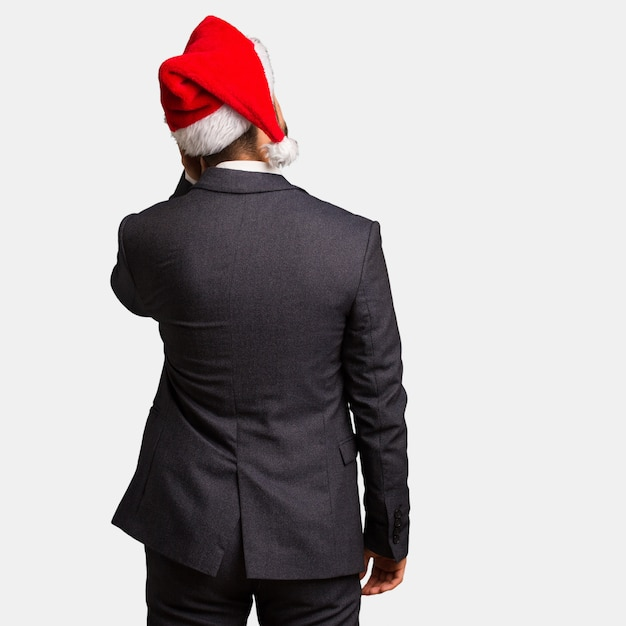 Young business man wearing santa hat from behind thinking about something