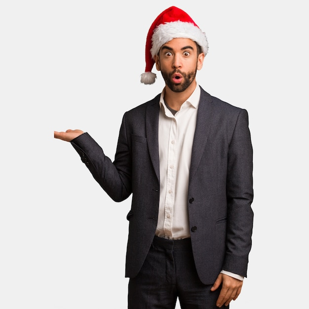 Young business man wearing santa hat holding something on palm hand