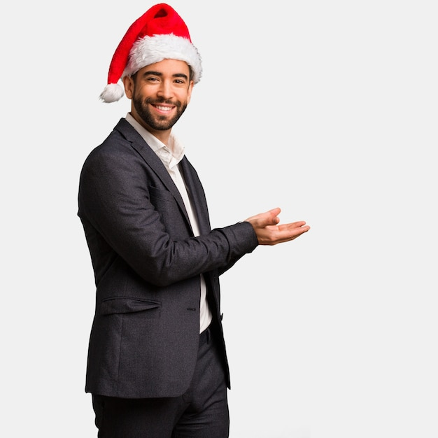 Young business man wearing santa hat holding something with hands