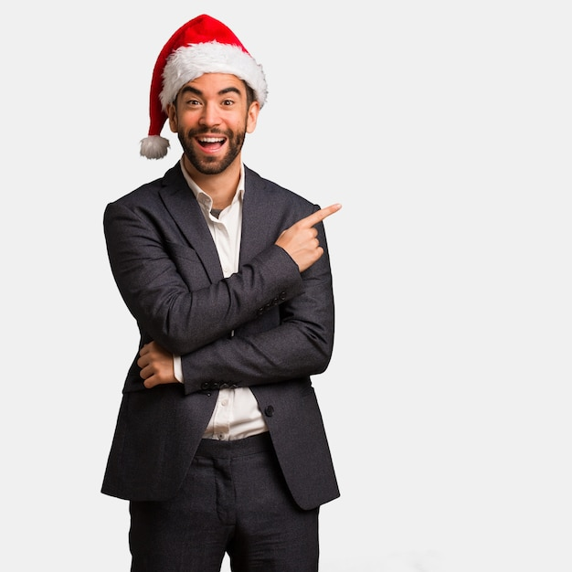 Young business man wearing santa hat pointing to the side with finger