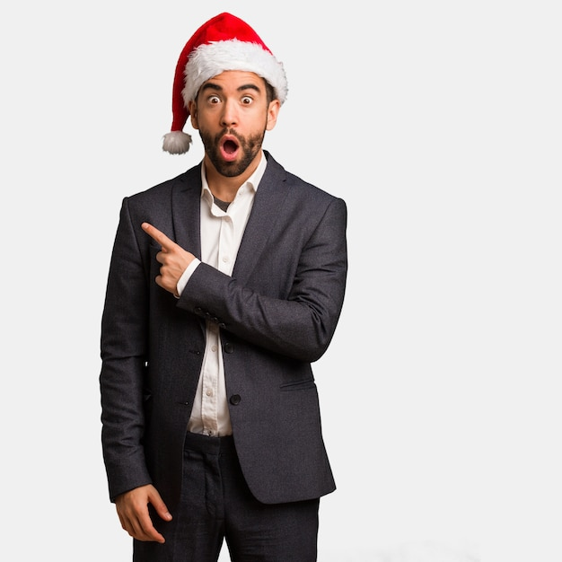 Young business man wearing santa hat pointing to the side