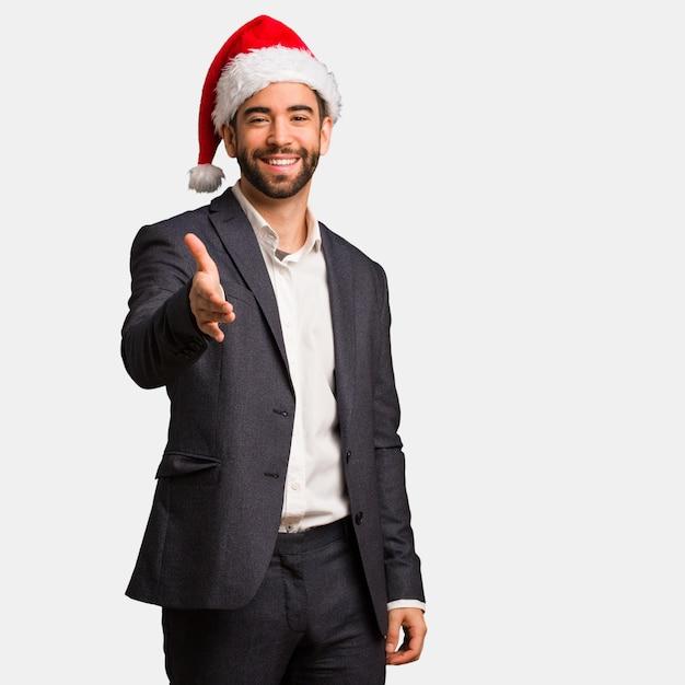 人に挨拶するために手を差し伸べているサンタの帽子