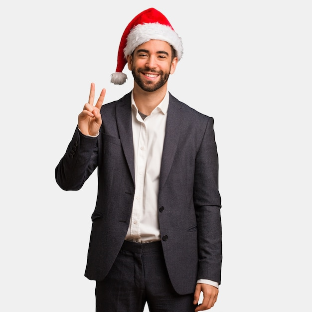 Young business man wearing santa hat showing number two