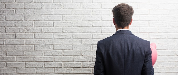 Young business man wearing a suit against a white bricks wall showing back, posing and waiting, looking back