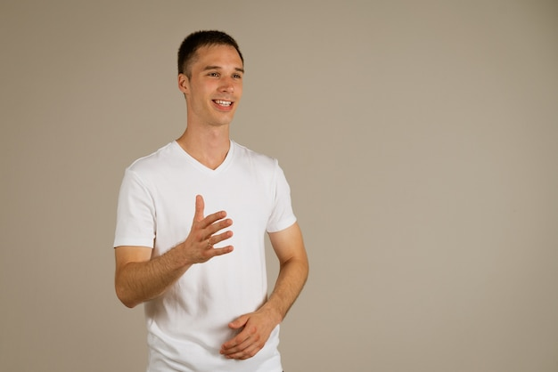 Young business man in a white t-shirt gesturing with his hands on a light wall