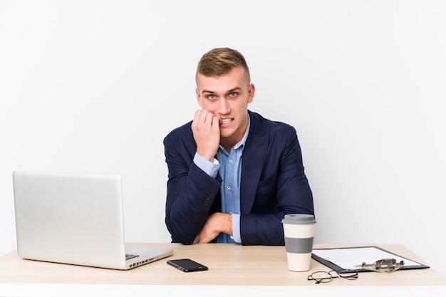 爪をかむ、緊張し、非常に心配しているラップトップを持つ若いビジネスマン。