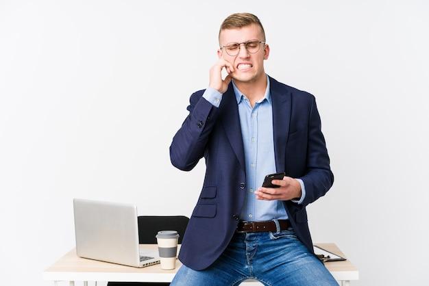 手で耳を覆うラップトップを持つ若いビジネス男。