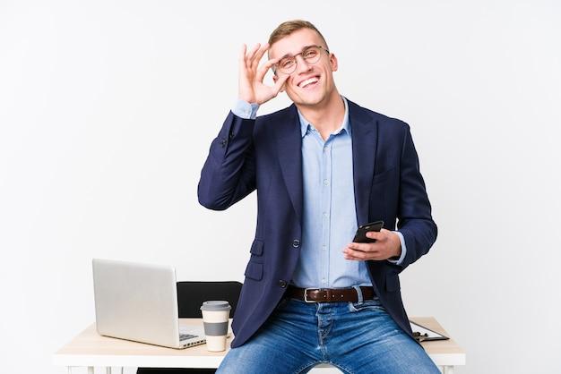 Молодой деловой человек с ноутбуком взволнован, держа одобренный жест на глазах.