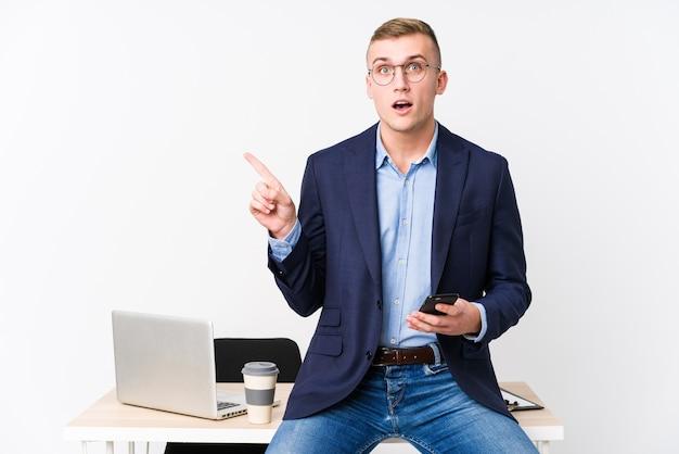 Молодой деловой человек с ноутбуком, указывая в сторону
