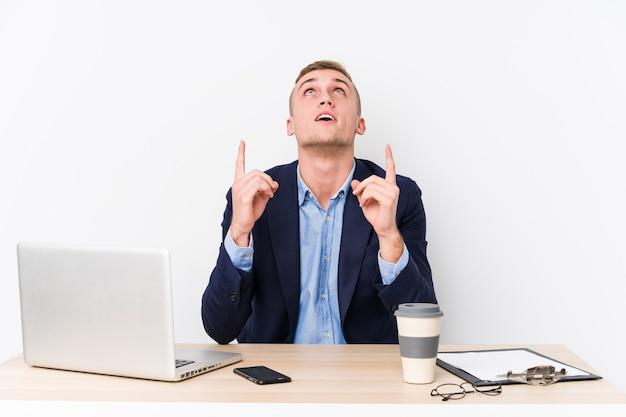 Молодой деловой человек с ноутбуком, указывая вверх с открытым ртом.