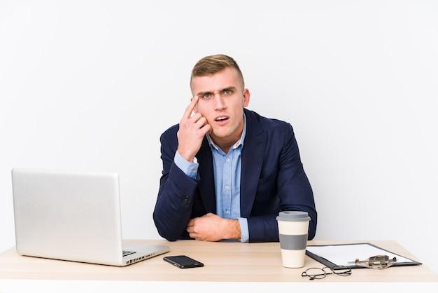 人差し指で失望のジェスチャーを示すラップトップを持つ若いビジネス男。
