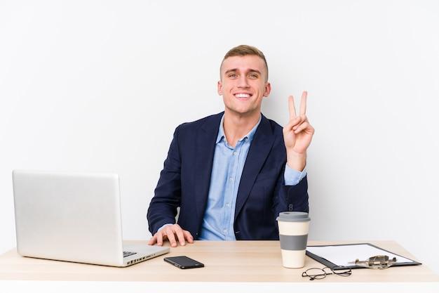 Молодой деловой человек с ноутбуком, показывая номер два пальцами.