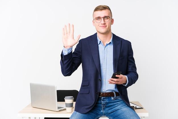 Молодой деловой человек с ноутбуком, улыбаясь веселым показом номер пять с пальцами.