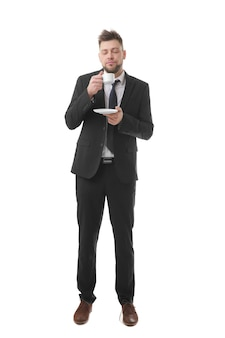 Young business man with closed eyes holding cup of coffee trying to wake up, isolated on white