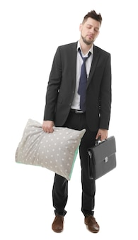 Young business man with closed eyes holding pillow and briefcase, isolated on white
