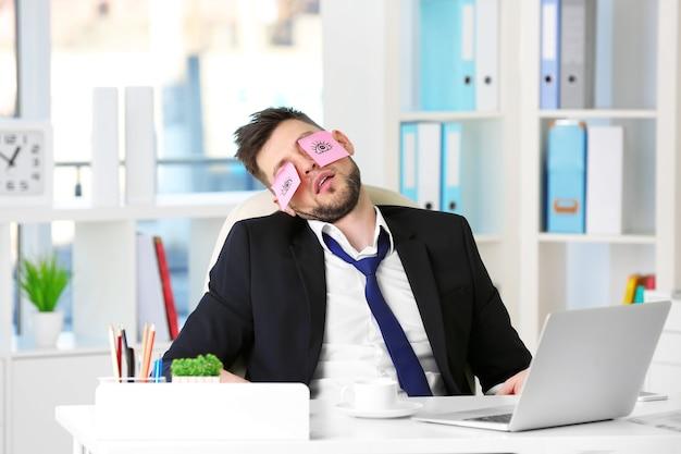Молодой деловой человек с фальшивыми глазами, нарисованными на бумажных наклейках, спит на рабочем месте в офисе