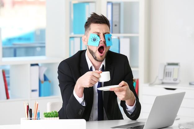 Молодой деловой человек с фальшивыми глазами, нарисованными на бумажных наклейках, зевая на рабочем месте в офисе