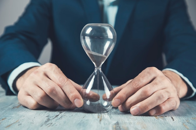 Young business man with hourglass on table