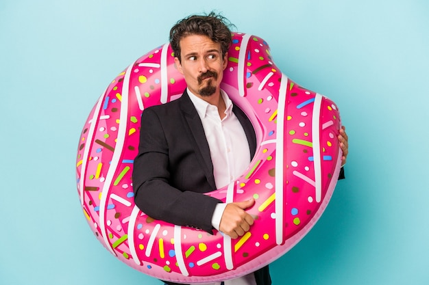 Young business man with inflatable donut isolated on blue background confused, feels doubtful and unsure.