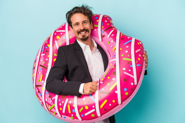 Young business man with inflatable donut isolated on blue background happy, smiling and cheerful.
