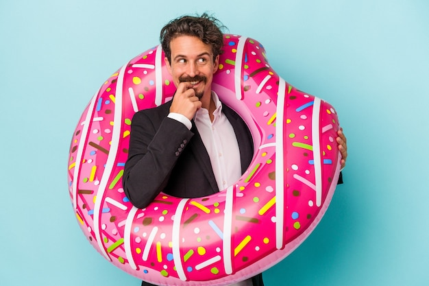 Young business man with inflatable donut isolated on blue background relaxed thinking about something looking at a copy space.