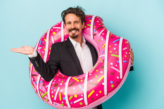 Young business man with inflatable donut isolated on blue background showing a copy space on a palm and holding another hand on waist.