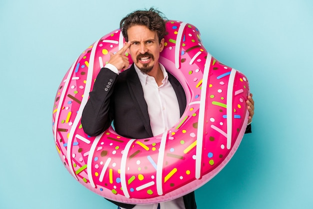 Young business man with inflatable donut isolated on blue background showing a disappointment gesture with forefinger.