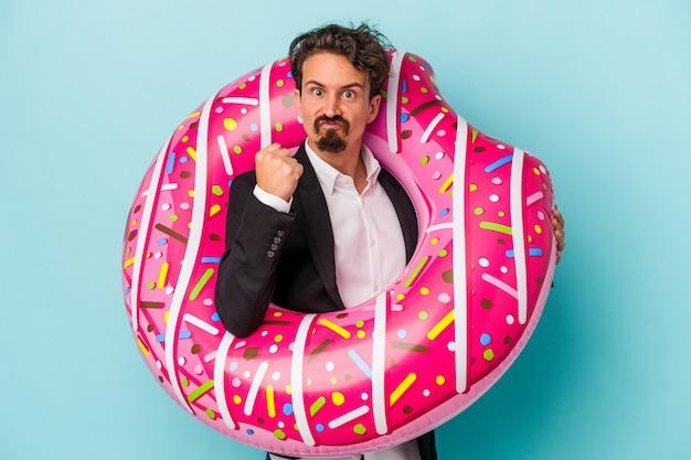 파란색 배경에 격리된 팽창식 도넛을 가진 젊은 사업가가 카메라에 주먹을 대고 공격적인 표정을 짓고 있습니다.
