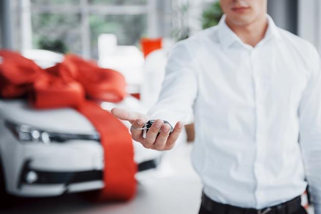 手に鍵を持っている若いビジネスマンは、キャビンで車を購入します。