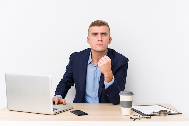 Young business man with a laptop showing fist with aggressive facial expression.