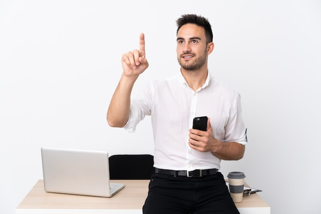 Young business man with a mobile phone in a workplace touching on transparent screen
