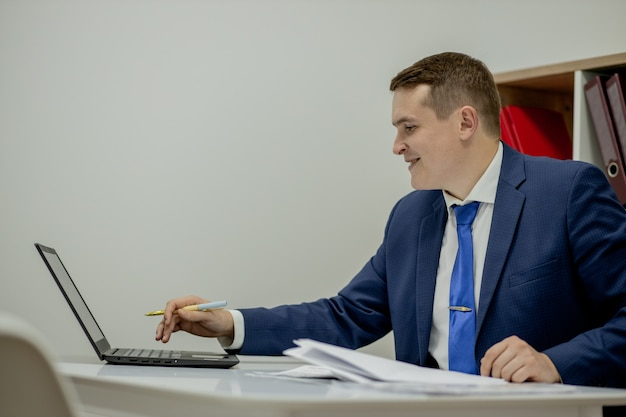 노트북과 책상에 서류와 함께 집에서 일하는 젊은 비즈니스 사람.