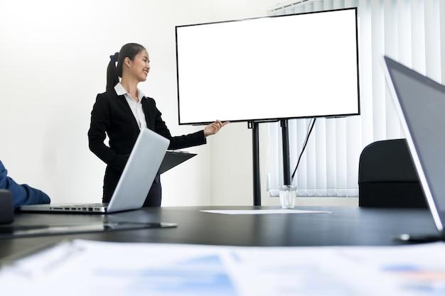 Молодой деловой человек, работающая презентация, используя телевидение пустого экрана