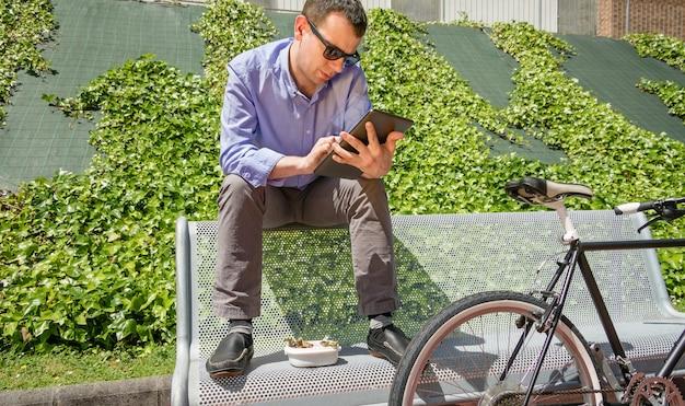 Молодой деловой человек работает с электронным планшетом во время обеденного перерыва, сидя на скамейке на открытом воздухе