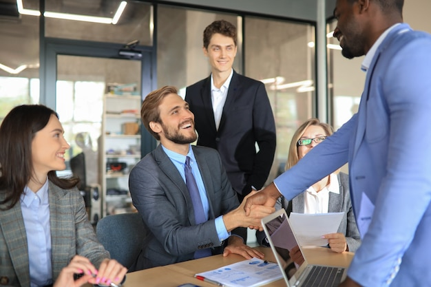 Young business men shaking hands and smiling while sitting at the desk in office.