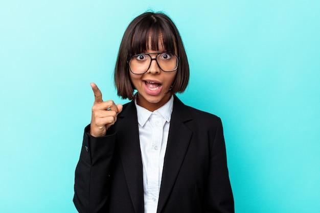 アイデア、インスピレーション コンセプトを持つ青の背景に分離された若いビジネス混血女性。